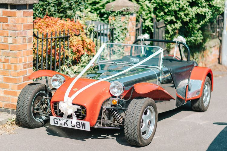 Red Kit Car Decorated with Ribbon   Arrival of the Bride   Hazel Gap Barn Wedding with Bride Arriving by Kit Car   Sarah-Jane Ethan Photography