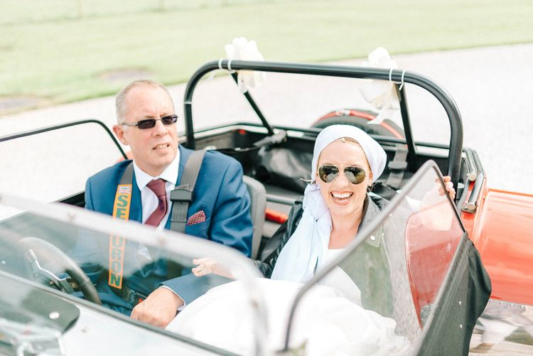 Red Kit Car Decorated with Ribbon   Arrival of the Bride   Bride in Leather Jacket, Headscarf and Aviator Sunglasses   Father of the Bride in Blue Suit   Hazel Gap Barn Wedding with Bride Arriving by Kit Car   Sarah-Jane Ethan Photography