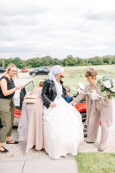 Red Kit Car Decorated with Ribbon   Arrival of the Bride   Strapless Sassi Holford Ballgown Wedding Dress with Belt   Bride in Leather Jacket, Headscarf and Sunglasses   Mother of the Bride in Grey Trouser Suit   Hazel Gap Barn Wedding with Bride Arriving by Kit Car   Sarah-Jane Ethan Photography