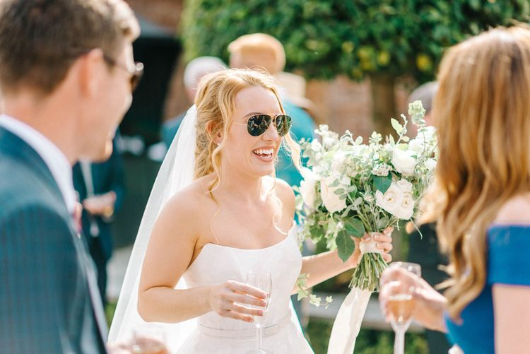 Bride in Strapless Sassi Holford Ballgown Wedding Dress with Belt   Bride Wearing Aviators   Bridal Bouquet with White Trailing Ribbon   White Flowers and Green Foliage   Hazel Gap Barn Wedding with Bride Arriving by Kit Car   Sarah-Jane Ethan Photography
