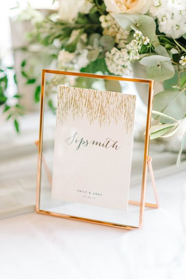 Wedding Reception Decor   Table Name   Copper Frame   White Flowers and Green Foliage    Hazel Gap Barn Wedding with Bride Arriving by Kit Car   Sarah-Jane Ethan Photography