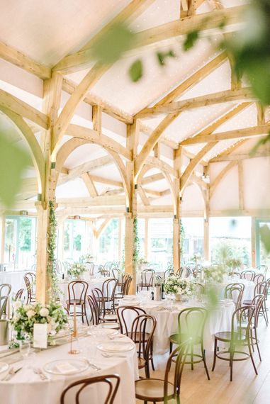 Wedding Reception Decor   Round Tables   Fairy Lights   White Flowers and Green Foliage    Hazel Gap Barn Wedding with Bride Arriving by Kit Car   Sarah-Jane Ethan Photography