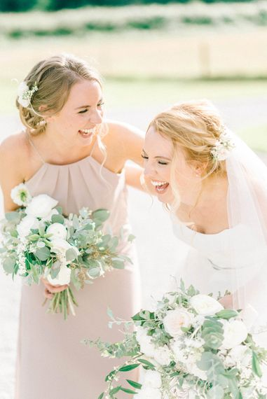 Bride in Strapless Sassi Holford Ballgown Wedding Dress with Belt   Bridesmaid in Grey Halterneck Dress   Loose Bouquets of White Flowers and Foliage   Hazel Gap Barn Wedding with Bride Arriving by Kit Car   Sarah-Jane Ethan Photography