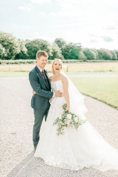 Bride in Strapless Sassi Holford Ballgown Wedding Dress with Belt   Groom in Blue Check Paul Smith Suit   Loose Bouquet of White Flowers and Foliage   Hazel Gap Barn Wedding with Bride Arriving by Kit Car   Sarah-Jane Ethan Photography