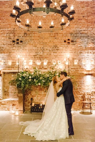 Bride in Strapless Sassi Holford Ballgown Wedding Dress with Belt   Groom in Blue Check Paul Smith Suit   Large Floral Fireplace Display   Candles   Hazel Gap Barn Wedding with Bride Arriving by Kit Car   Sarah-Jane Ethan Photography