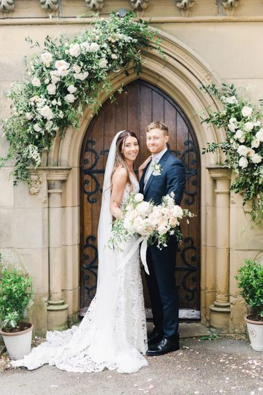 Bride and Groom After Ceremony in Doorway with Flowers