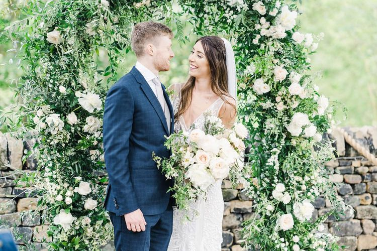 Bride and Groom In Front of Flower Arch