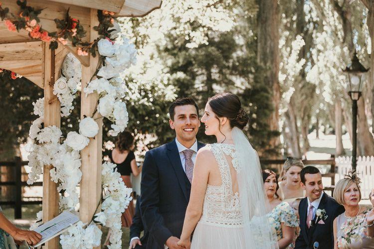 Outdoor Home Wedding Ceremony with Bride in Pronovias Danaia Wedding Dress and Groom in Navy Moss Bros. Suit
