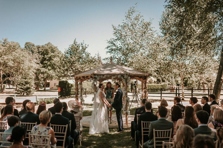 Outdoor Home Wedding Ceremony in Front of Pergola with Bride in Pronovias Danaia Wedding Dress and Groom in Navy Moss Bros. Suit