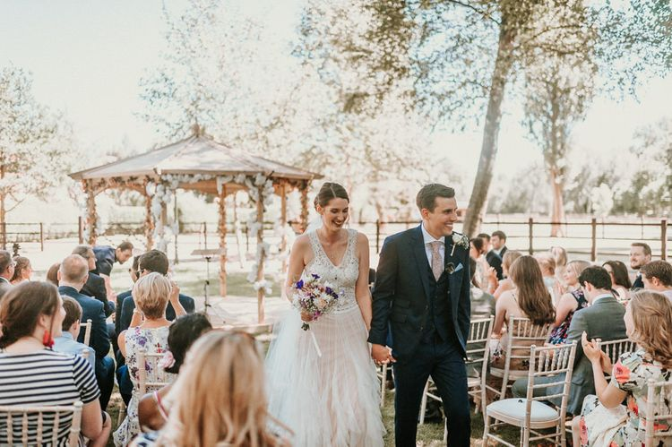 Bride in Pronovias Danaia Wedding Dress and Groom in Navy Moss Bros. Suit Walking up the Aisle Just Married