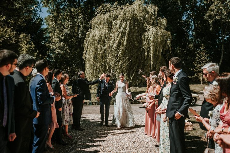 Confetti Moment with Bride in Pronovias Danaia Wedding Dress and Groom in Navy Moss Bros. Suit