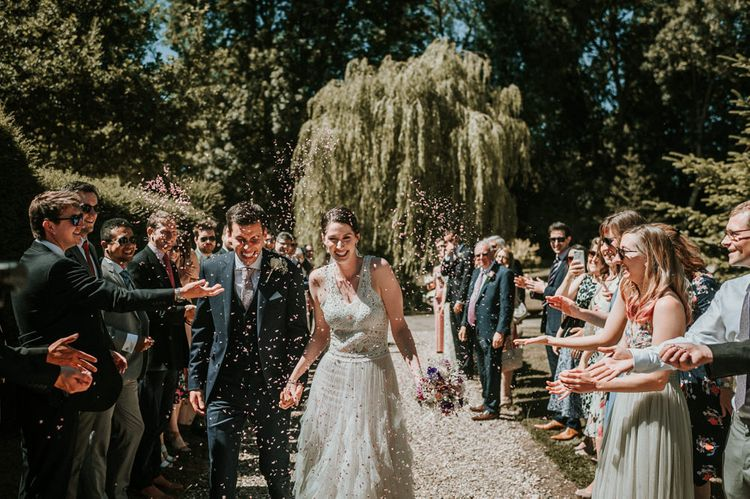 Happy Confetti Moment with Bride in Pronovias Danaia Wedding Dress and Groom in Navy Moss Bros. Suit