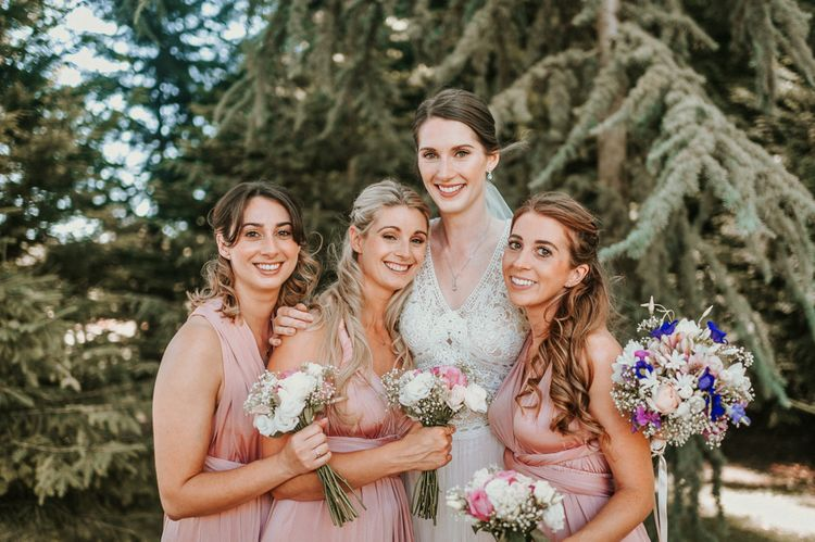 Bridal Party Portrait with Bridesmaids in Pink Oasis Dresses and Bride in Pronovias Danaia Wedding Dress