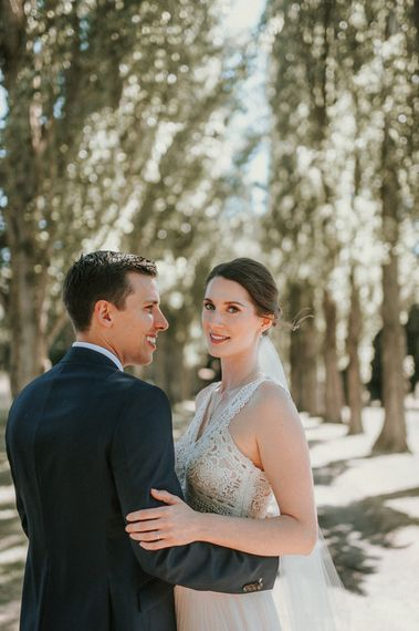 Bride in Pronovias Danaia Wedding Dress and Groom in Moss Bros. Suit  Embracing in The Woods
