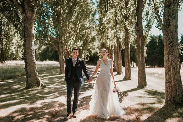 Bride in Pronovias Danaia Wedding Dress and Groom in Moss Bros. Suit Holding Hands in the Woods
