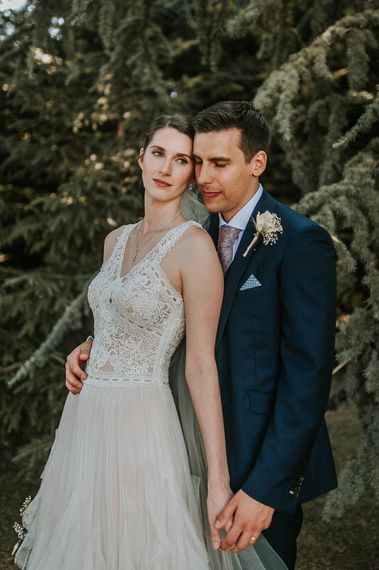 Bride in Pronovias Danaia Wedding Dress and Groom in Moss Bros. Suit Embracing