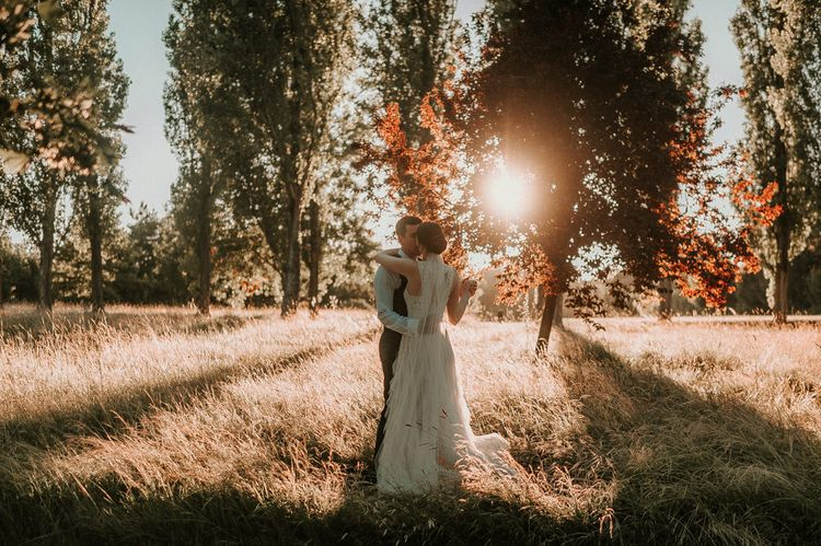 Golden Hour Field Portrait with Bride in Pronovias Danaia Wedding Dress and Groom in Moss Bros. Suit