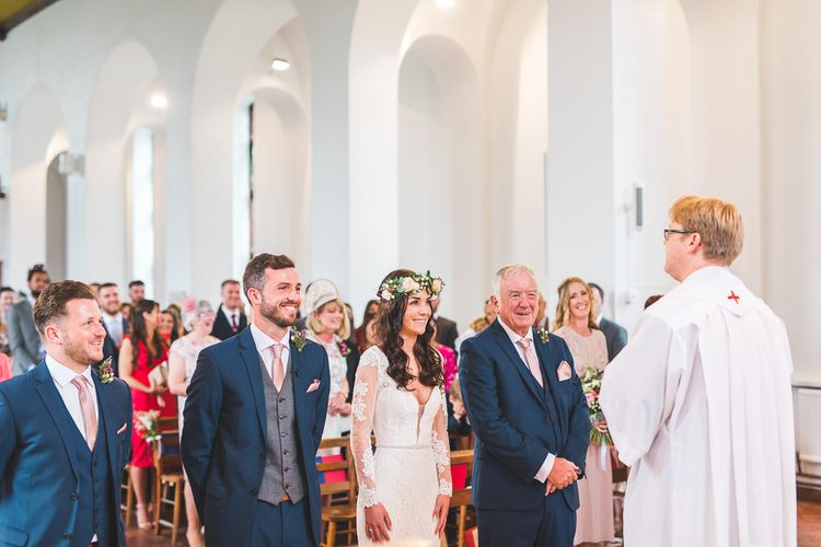 Church Wedding Ceremony | Bride in Long Lace Sleeve Mikaella Bridal Gown & Flower Crown | Groom in Navy Moss Bros Suit | Spring, Boho, Festival Themed Wedding with Flower Crowns, Pastel Flowers & Street Food Vans at  Painshill Park, Surrey | Kirsty Mackenzie Photography | Alice Underwood Films