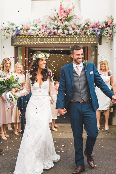 Confetti Moment | Bride in Long Lace Sleeve Mikaella Bridal Gown & Flower Crown | Groom in Navy Moss Bros Suit | Spring, Boho, Festival Themed Wedding with Flower Crowns, Pastel Flowers & Street Food Vans at  Painshill Park, Surrey | Kirsty Mackenzie Photography | Alice Underwood Films