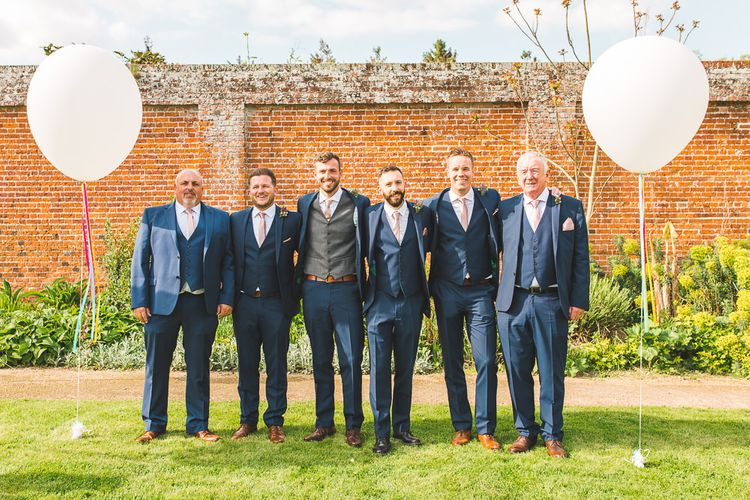 Groomsmen in Navy Moss Bros Suits | Giant Balloons | Spring, Boho, Festival Themed Wedding with Flower Crowns, Pastel Flowers & Street Food Vans at  Painshill Park, Surrey | Kirsty Mackenzie Photography | Alice Underwood Films