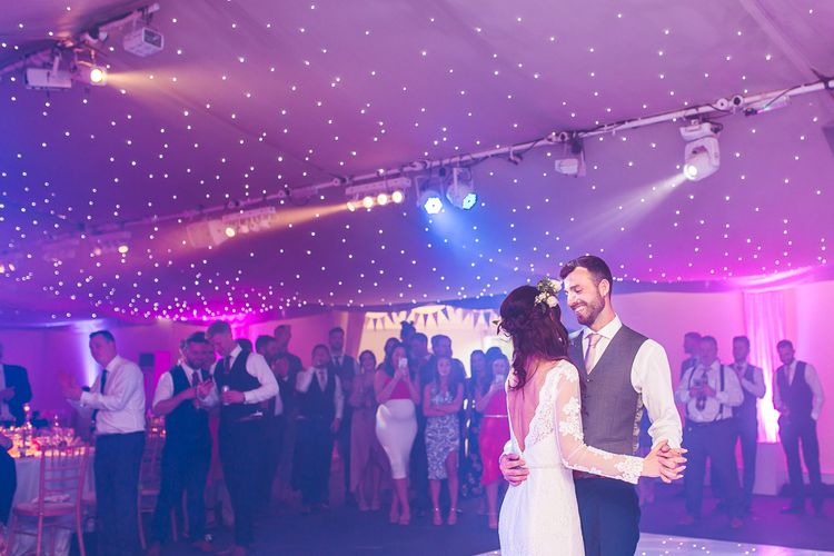 First Dance | Bride in Long Lace Sleeve Mikaella Bridal Gown & Flower Crown | Groom in Navy Moss Bros Suit | Spring, Boho, Festival Themed Wedding with Flower Crowns, Pastel Flowers & Street Food Vans at  Painshill Park, Surrey | Kirsty Mackenzie Photography | Alice Underwood Films