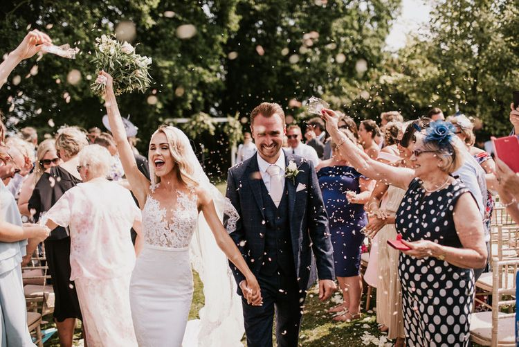 Confetti Moment with Bride in Pronovias Wedding Dress and Groom in Moss Bros. Suit