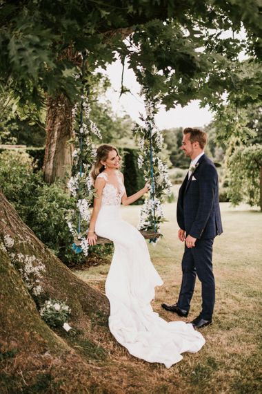 Bride in Pronovias Wedding Dress Sitting on a Ivy Covered Swing with Groom in Moss Bros. Suit  Standing By