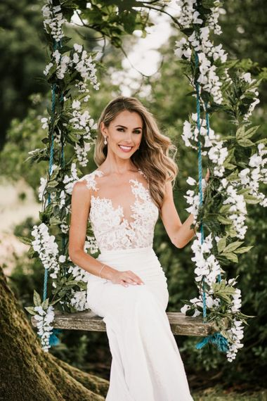 Bride in Pronovias Wedding Dress Sitting on a Ivy Covered Swing