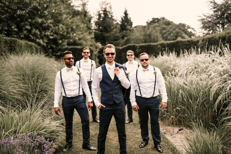 Stylish Groomsmen in Braces and Groom in Check Moss Bros. Suit