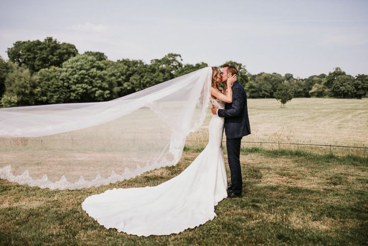 Bride in Vicenta Pronovias Wedding Dress and Groom in Navy Check Moss Bros Suit