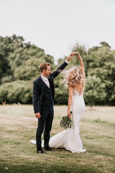 Groom in Navy Check Moss Bros Suit Twirling Bride in Vicenta Pronovias Wedding Dress