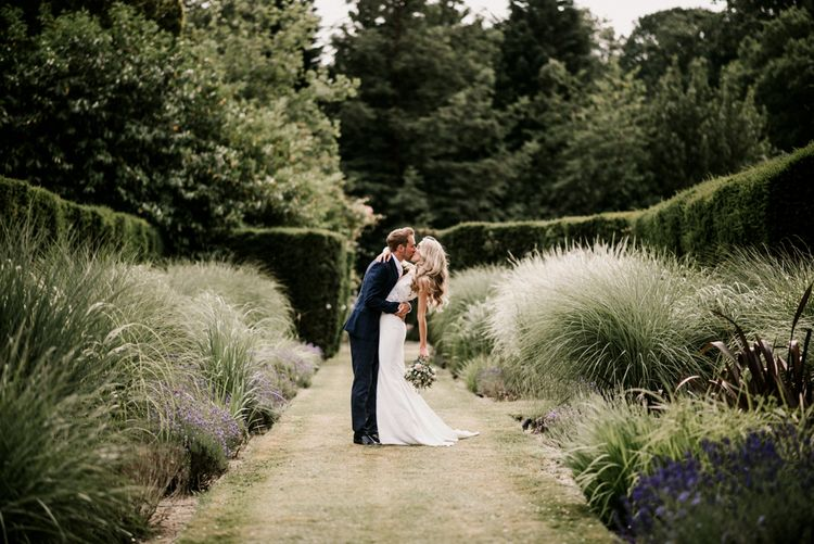 Bride in Vicenta Pronovias Wedding Dress and Groom in Navy Check Moss Bros Suit Kissing