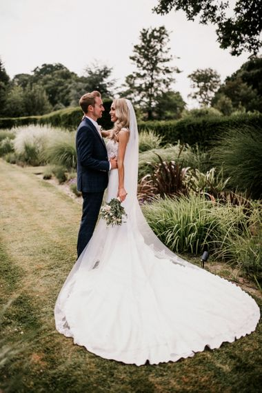 Bride in Vicenta Pronovias Wedding Dress and Groom in Navy Check Moss Bros Suit Hugging