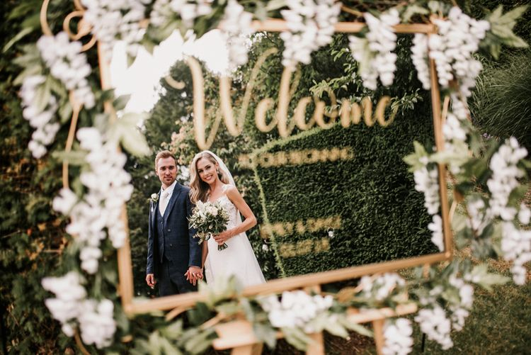 Gold Framed Mirror Wedding Welcome Sign with Reflection of Bride and Groom
