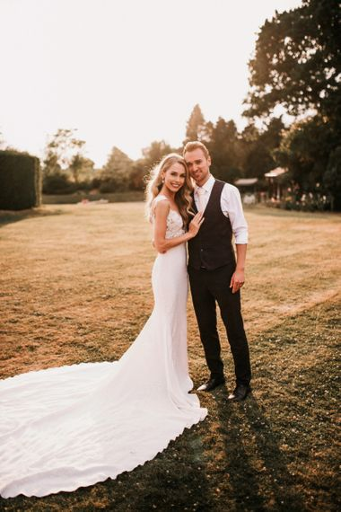 Golden Hour Portrait with Bride in Vicenta Pronovias Wedding Dress and Groom in Navy Check Moss Bros Suit