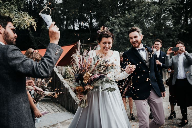 Confetti Moment with Bride in Silver Skirt and Groom in Pink Chinos and Navy Blazer
