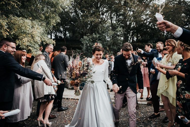 Confetti Moment in the Woods with Bride in Silver Skirt and Groom in Pink Chinos and Navy Blazer