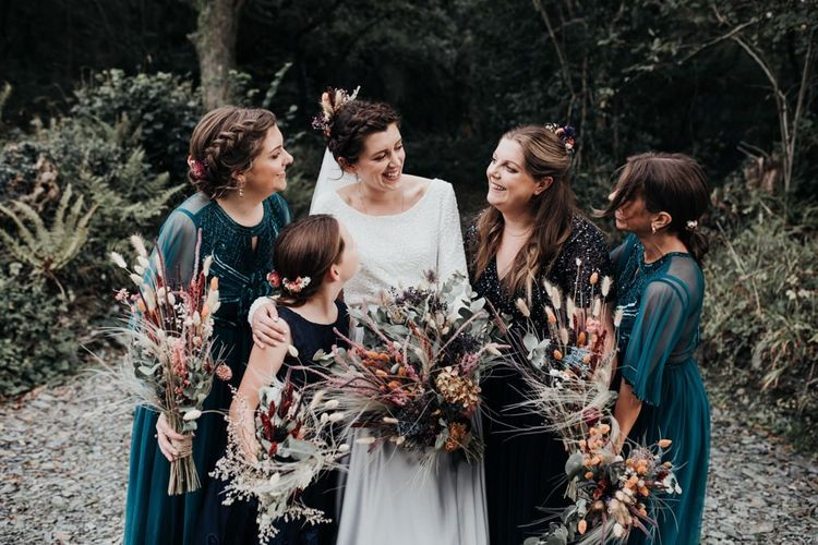 Bridal Party Laughing in the Woods with Bridesmaids in Emerald Green & Navy Dresses Holding Dried Flower Bouquets