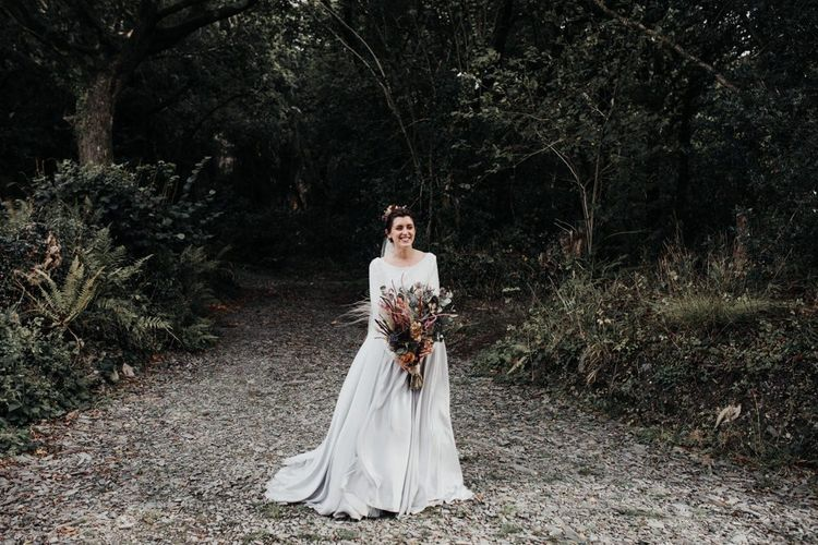 Bride in Contemporary Mila Mira Wedding Dress with Silver Skirt and White Top Holding an Autumn Wedding Bouquet