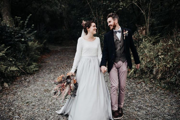 Boho Bride in Contemporary Mila Mira Wedding Dress with Silver Skirt and White Top and Groom in Pink Chinos, Wool Waistcoat and Navy Blazer