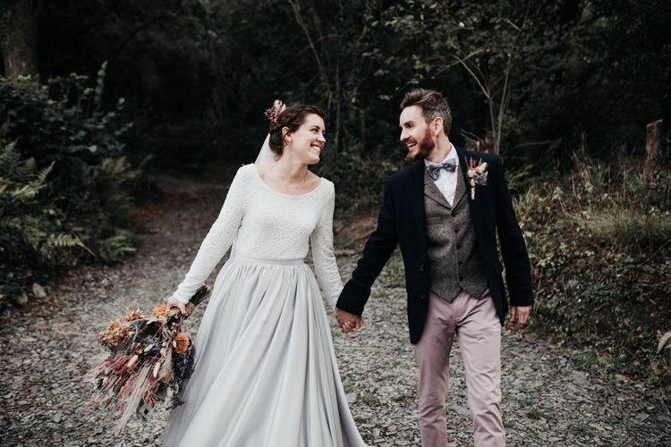 Stylish Bride and Groom Holding Hands in the Woods in Silver Skirt Separates and Pink Chinos