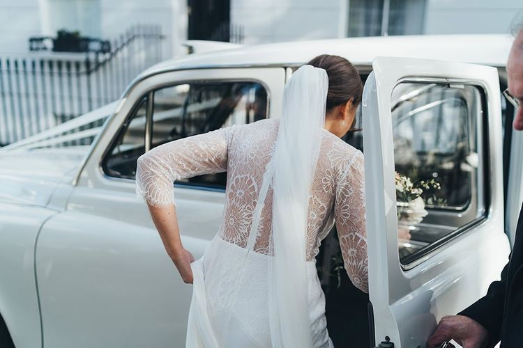 Bride getting in a Vintage London Taxi in a Lace Back Wedding Dress
