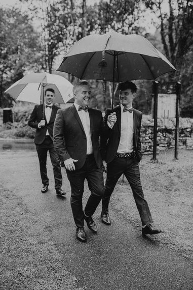 Groomsmen in Suits and Bow Ties Under Umbrellas
