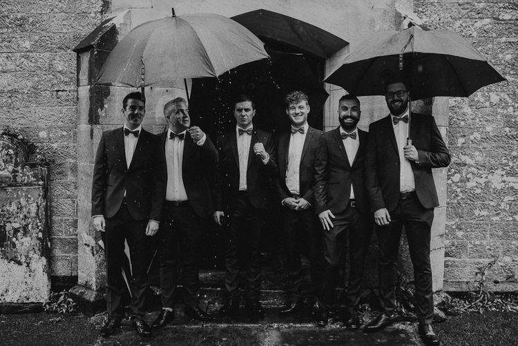 Groomsmen Standing Under Umbrellas