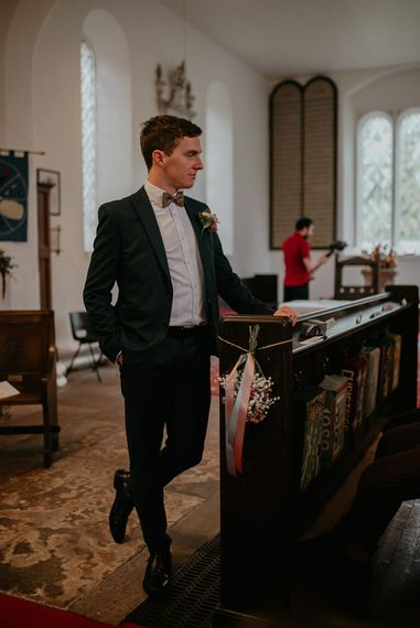 Groom at the Altar in Black Suit and Bow Tie