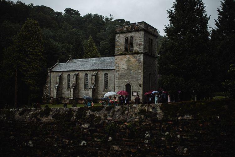 Church Wedding with Guests Standing Under Umbrellas