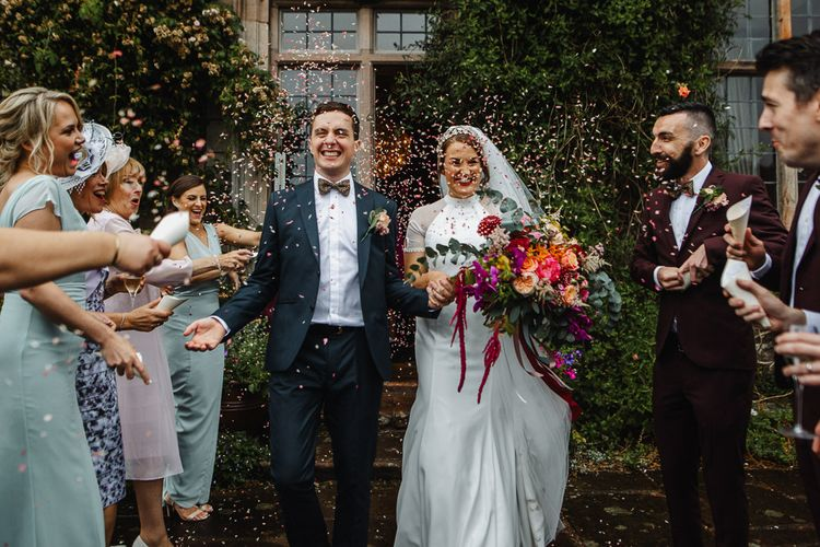 Confetti Moment with Bride in Bespoke Dress and Groom in Suit & Bow Tie