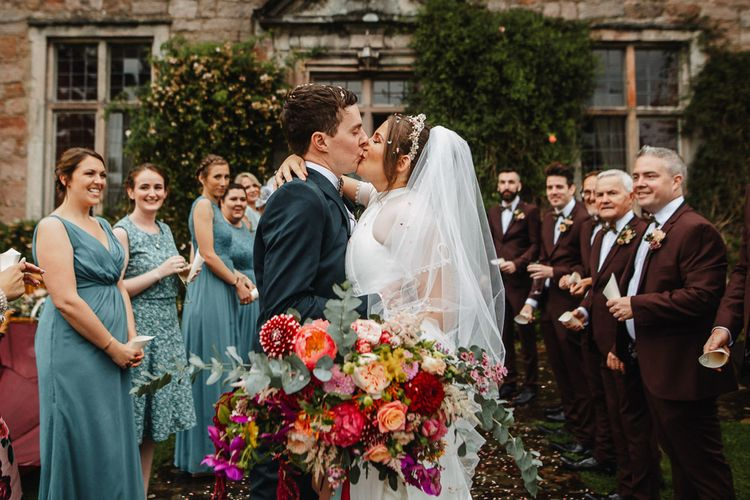 Bride and Groom Kissing Whilst Holding a Pink Wedding Bouquet