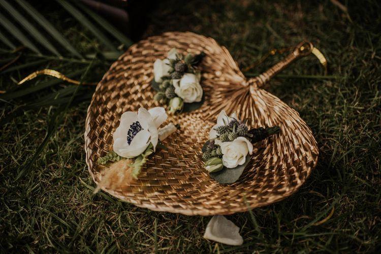 Rattan fans with floral buttonholes