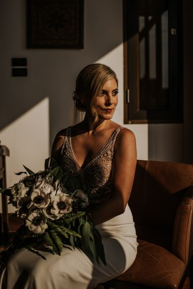 Bride in beaded bodysuit with bouquet and updo